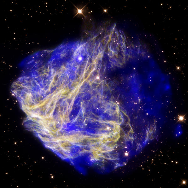 'This composite image of data from Chandra (blue) and Hubble (yellow and purple) depicts the scene of a supernova explosion's aftermath.  The X-ray data reveal a bullet-like structure to the lower right that appears to have been blown out of the remnant.   The detection of the bullet, which is traveling at some 5 million miles per hour, is evidence that the explosion that created the remnant was not symmetrical.'