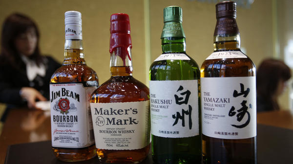 The Japanese drinks company Suntory plans to buy Beam Inc., which includes Jim Beam and Maker's Mark bourbon. They are shown next to Suntory's Yamazaki and Hakushu whiskies at Suntory headquarters in Tokyo on Tuesday. The deal makes Suntory one of the world's leading drinks companies in an industry where a handful of companies increasingly dominate the global market.