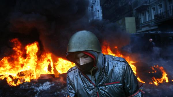 A protester walks pass burning tires in central Kiev, Ukraine, on Thursday.