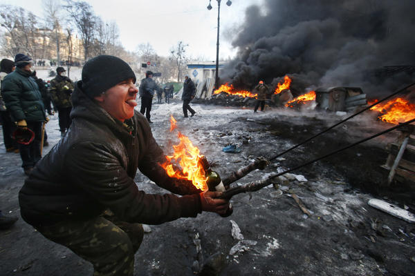 A protester prepares to hurl a Molotov cocktail at police in downtown Kiev, Ukraine. Ukrainian opposition leaders issued an ultimatum to the president: call for an early election or face attack.