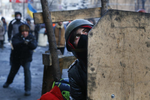 Protesters shield themselves during battles with police.