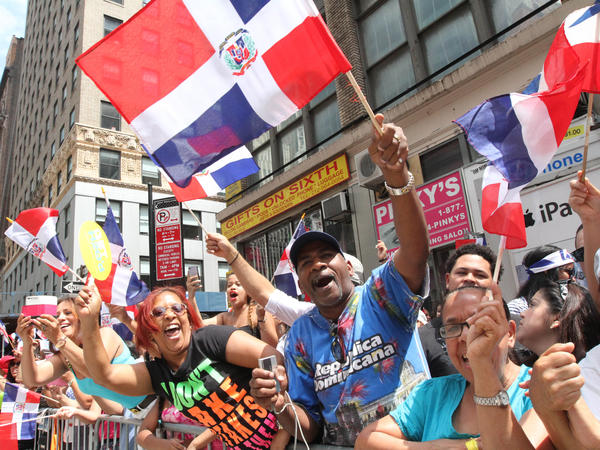 Spectators react as they watch the Dominican Day Parade in New York City last summer.