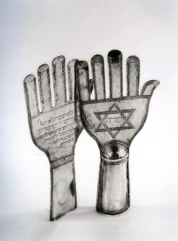 These early 20th-century hand-shaped Torah finials are unique to the Jewish communities of Iran and Iraq and are inspired by hand-shaped banners, called <em>alam</em>, that are carried by Shiite Muslims on the holy day of Ashura.