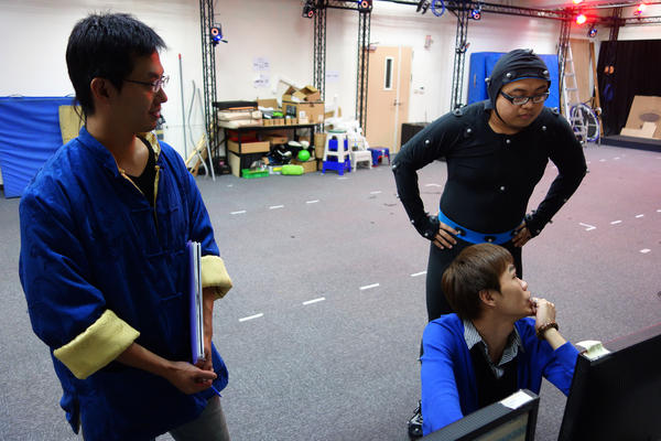 The motion-capture team at Next Media Animation. The actor (in the leotard) is wearing sensors that the 40 cameras mounted in the studio will capture to help animators render his movements digitally.