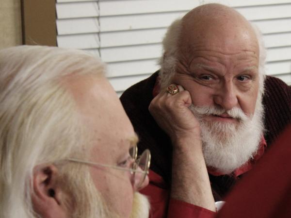 Santa Ron Campbell listens to his fellow Santas debriefing about how this year went. (Eric Mennel/WUNC)