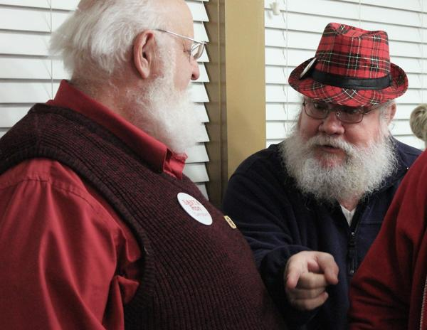 Santa Ellis Stephens shares tips with Santa Ron Campbell. (Eric Mennel/WUNC)