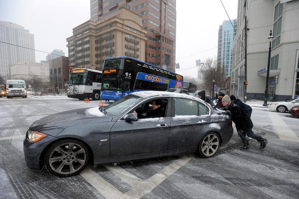 Good Samaritans help push a car past a patch of ice in Atlanta during the storm. Officials declared a state of emergency in multiple Southern states, including Georgia.