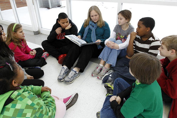 Joyce Cook, an instructional aide, reads <em>Snowflake Bentley</em> to a group of fifth-graders stranded at Oak Mountain Intermediate School because of snow and ice in Indian Springs, Ala.