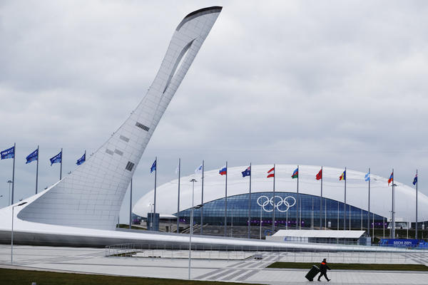 A worker walks past the Olympic torch and the Bolshoy Ice Dome in the Olympic Park as preparations continue Thursday ahead of the Sochi Winter Games. Russia has spent $50 billion on the 2014 games — the most expensive in history.
