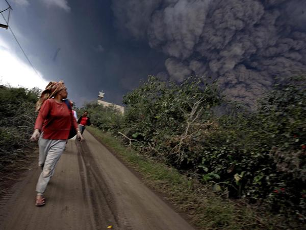 Indonesian villagers flee as Mt. Sinabung spews volcanic materials in Karo, North Sumatra, Indonesia, on Saturday.