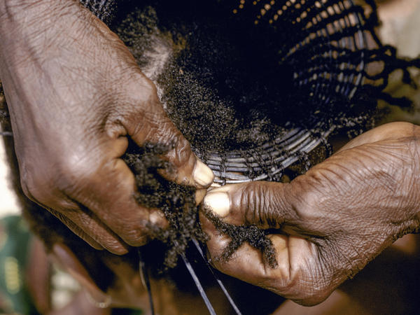 Weaving a traditional Mangbetu hairstyle in 1970, Medje village, Congo.