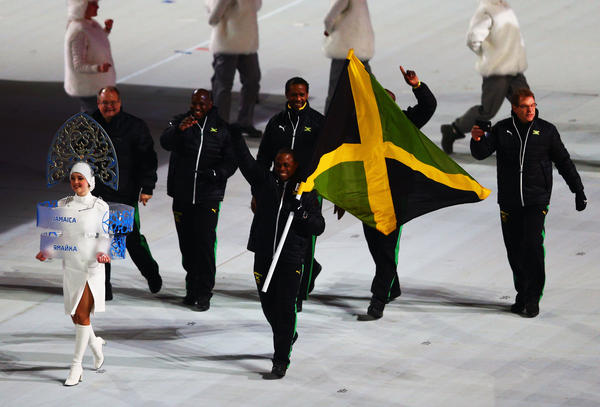 Bobsled racer Marvin Dixon and the Jamaican Olympic team get a warm welcome while carrying their country's flag.