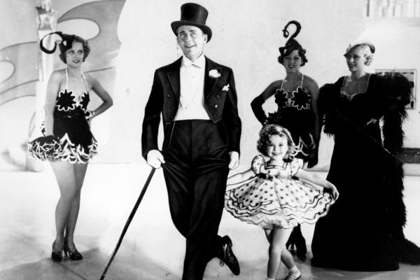 Temple curtsies in a promotional photo for the musical <em>Stand Up and Cheer</em> with James Dunn in 1934.