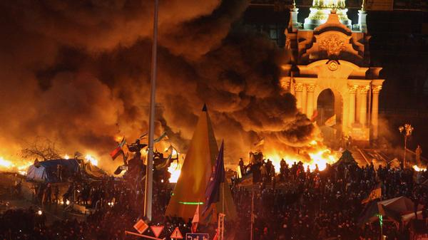 Smoke from exploding fireworks and fires billows into the night sky as Ukrainians gather at Independence Square during continuing protests in Kiev on Tuesday.