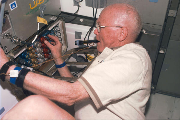 Glenn checks out support equipment for an experiment during the shuttle's orbit above Earth on Nov. 4, 1998.