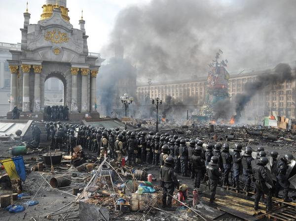 Riot police officers stand in Kiev's Independence Square on Wednesday as smoke rises from protesters' burning barricades.