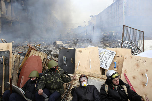 Anti-government demonstrators rest at a barricade near the site of clashes with Interior Ministry members and riot police in Kiev. Police there attacked an opposition camp at the center of the massive anti-government protests that began in November.