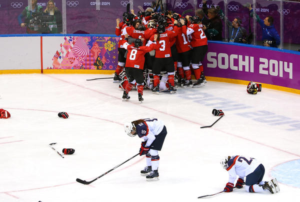 The Canadian team celebrates Marie-Philip Poulin's winning overtime goal as American players try to recover from a game that seemed to be within their grasp in Sochi Thursday.