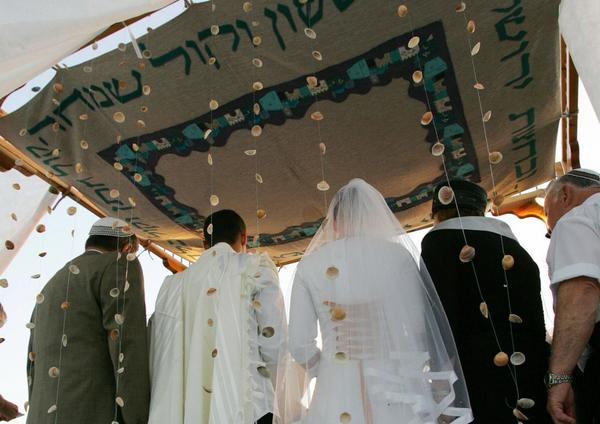 An couple stands under a 'chupa', a Jewish altar, during a traditional wedding ceremony.  (David Furst/AFP/Getty Images)