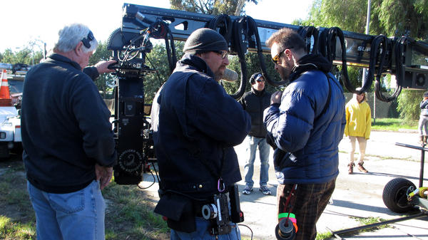 "On location for <em>Walk of Shame,</em> camera crew members Larry Nielsen (center) and Milan ""Miki"" Janicin (right) help set up a crane shot. The wireless focus remote Nielsen will use is hanging from that purple carabiner on his jacket."