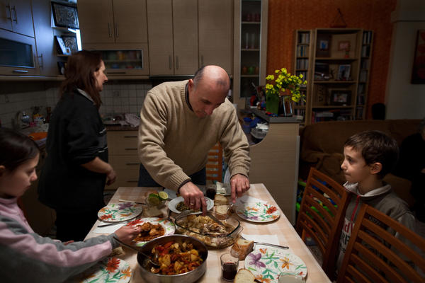 Aivatzidis cuts up leftovers before his family sits down to a meal in Athens.
