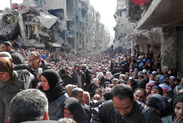 Masses of refugees wait in line to receive food aid distributed in the Yarmouk camp on Jan. 31 in Damascus, Syria.