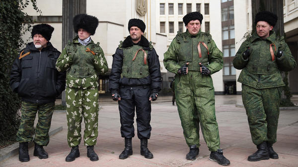 Cossacks stand guard at the entrance to the Crimean Parliament building on Friday in Simferopol, Ukraine. Russian Cossacks, some heavily armed, have taken up guard duties at road checkpoints, border crossings and other key facilities that were previously guarded by local, pro-Russian militants across Crimea in recent days.