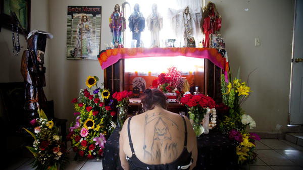 Claudia Rosales kneels in front of her home altar devoted to <em>Santa Muerte,</em> or Saint Death. Rosales put up a statue of the saint in the city that was taken down by the mayor of Matamoros.