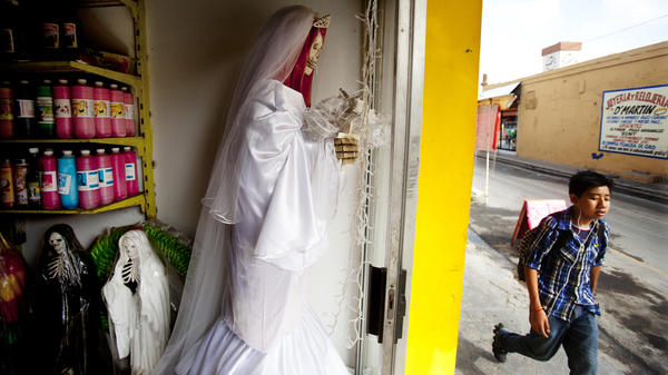 <em>La Patrona,</em> a <em>botanica</em> owned by Senora Tina in Matamoros, Mexico, sells statues, candles and mini figurines of <em>Santa Muerte.</em> Senora Tina says the cult of Saint Death is growing fast north of the border, where she has many clients who travel to Matamoros for consultations.