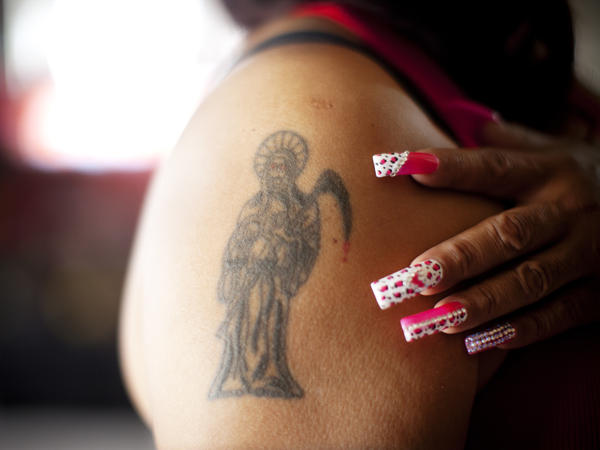 Claudia Rosales has several tattoos of <em>Santa Muerte</em> on her arms, chest and back.