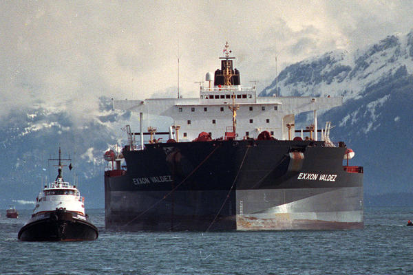 Tugboats pull the crippled Exxon Valdez tanker toward Naked Island. The ship spilled 11 million gallons of oil into Prince William Sound.