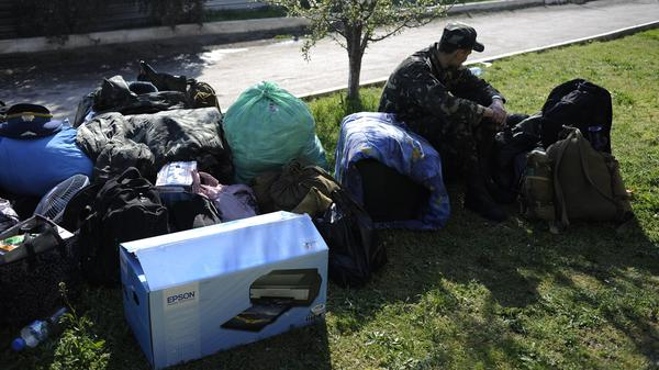 A Ukrainian serviceman sits next to gear and bags before leaving the Belbek airbase near Sevastopol, Crimea, Friday. Ukraine is withdrawing its troops and weapons from Crimea, now controlled by Russia.