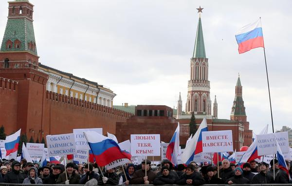 "Russians in Moscow's Red Square hold banners reading, ""Love You Crimea!"" ""Together For All Time"" and ""Obama, Think About Alaska!"" during a March 18 rally celebrating the annexation of Crimea."