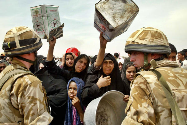 Iraqi women reach out with empty water containers as British soldiers arrive to supply the outskirts of Basra with drinking water in 2003.
