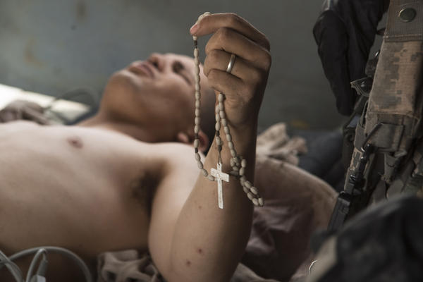 Lance Cpl. Blas Trevino of the 1st Battalion, 5th Marines, clutches his rosary beads as he is rescued onto a medevac helicopter. He was shot in the stomach outside Sangin, in the Helmand province of southern Afghanistan, in June 2011.