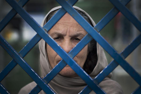 Afghan prisoner Fauzia stares out of the prison bars at Badam Bagh in 2013. Fauzia is the oldest woman in jail and has served seven years. She will serve a 17-year sentence for killing her husband and her daughter-in-law.