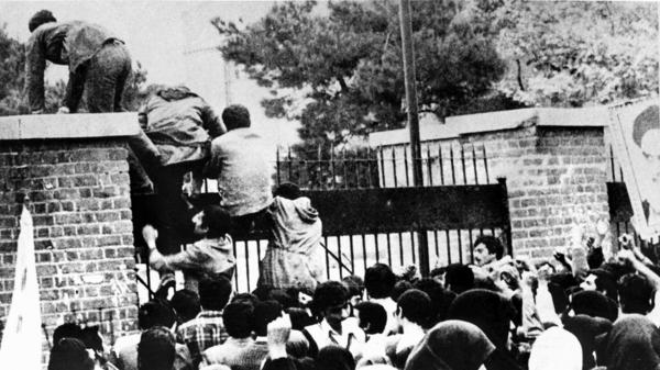 Iranian students climb over the wall of the U.S. Embassy in Tehran during the Iranian Revolution, Nov. 4, 1979. The students went on to seize the embassy staff, and hold 52 of them as hostages for 444 days.