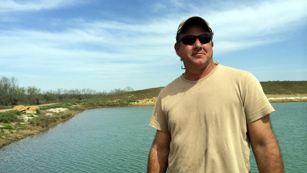 Rancher Darrell Brownlow stands in front of the pond Chesapeake Energy dug on his land when he leased part of it to the company. It will allow him to irrigate, and the oil money means he can afford to rebuild the ranch and bring back the cattle.