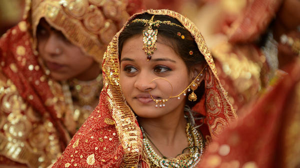 An Indian bride at a mass wedding. Whether Hindu, Christian, Buddhist or Muslim, bedecking an Indian bride in gold is believed to invest her with good fortune.
