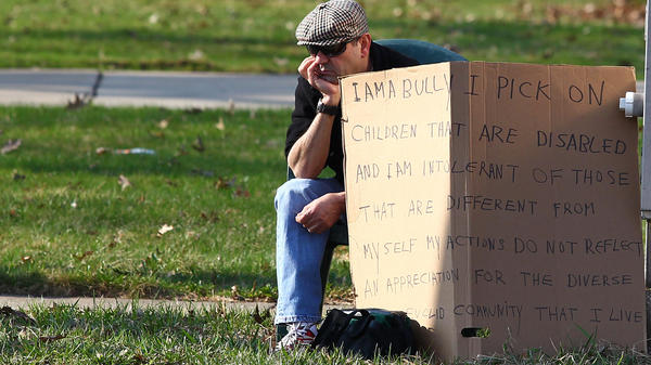 "Edmond Aviv, 62, sits with a sign at a street corner in the Cleveland suburb of South Euclid Sunday. Aviv, who called his neighbor ""monkey momma"" as she held her adopted, disabled African-American children, was ordered by a judge to display the sign."