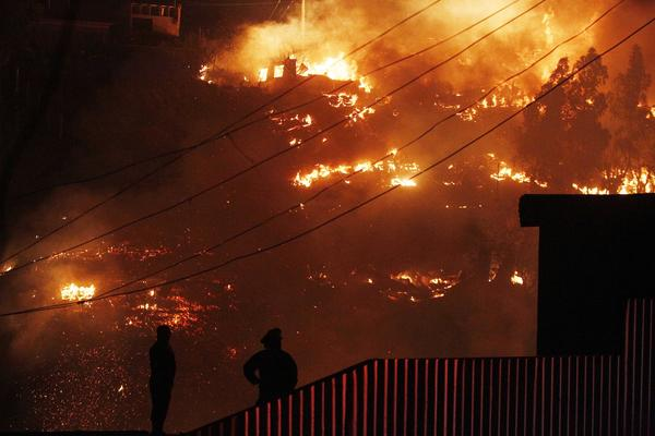 Emergency responders watch as an out-of-control forest fire destroys homes in Valparaiso, Chile, Sunday. The fire is blamed for destroying thousands of homes.