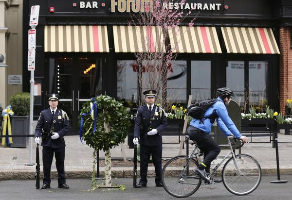 A Boston Police honor guard is posted outside the Forum restaurant Tuesday, the site of the second of two bombs that exploded near the finish line of the 2013 Boston Marathon.