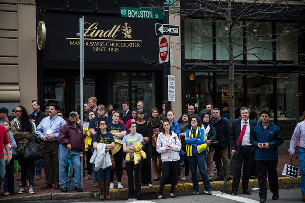 People watch a billboard television screen broadcasting the ceremony commemorating the one-year anniversary of the 2013 Boston Marathon Bombing on Tuesday.