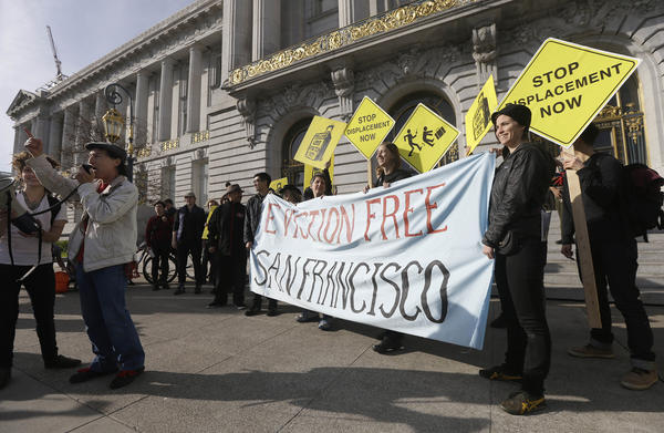 Members of the Housing Rights Committee of San Francisco and other activists protest outside of City Hall in San Francisco, Tuesday, Jan. 21, 2014. San Francisco officials are set to vote on a plan to start regulating employee shuttles for companies like Google, Facebook and Apple, charging a fee for those that use public bus stops and controlling where they load and unload. Private shuttle buses have created traffic problems, blocking public bus stops during peak commute hours. (Jeff Chiu/AP)