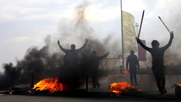 Iraqi Sunni masked protesters burn tires to block the main highway to Jordan and Syria, outside Fallujah, Iraq, on Dec. 30. Violence has returned to Iraq's Anbar province, with discontented ordinary Sunnis joining forces with al-Qaida-linked militants battling the Iraqi government.