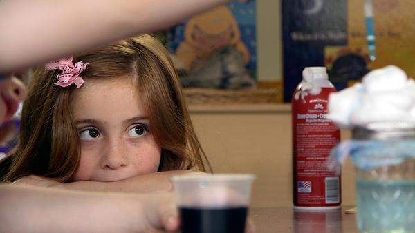 Preschool student Stormy Frazier watches an experiment unfold in Nikki Jones' classroom.