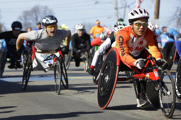 Participants in the wheelchair division of the marathon cross the starting line in Hopkinton.