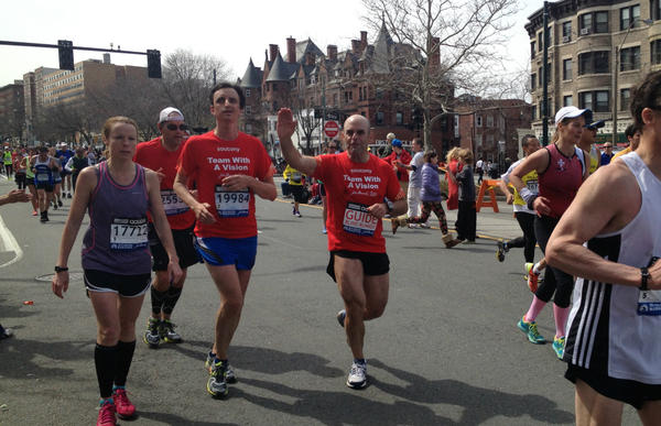 Peter Sagal, waving, runs next to William Greer around Mile 24 of the 2013 Boston Marathon. This picture was taken roughly 20 minutes before the bombs went off. (Linda McIntosh/Courtesy)