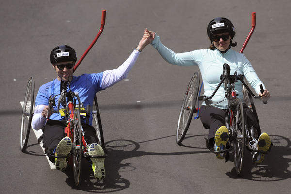Boston Marathon bombing survivors Patrick Downes and Jessica Kensky cross the finish line. The newlyweds each lost a leg during the bombing.