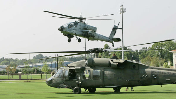An airborne Apache attack helicopter takes off above a Black Hawk helicopter from the South Carolina Army National Guard base in Eastover, S.C., in 2007. The Army is planning to move all the National Guard's Apache helicopters to the regular Army, a move opposed by many in the Guard.